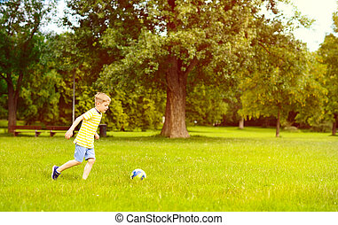Sporting boy plays football in sunny park - Sporting little...