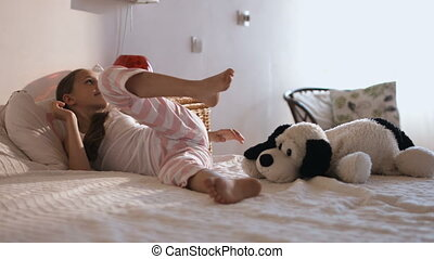 Close-up portrait of child in soft warm pajama waking up at...