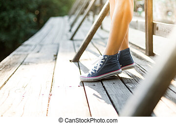 Young woman standing on a bridge in jeans sneakers