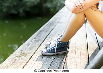 Young woman on a wooden bridge in jeans sneakers - Young...