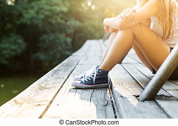 Young woman on a wooden bridge in jeans sneakers