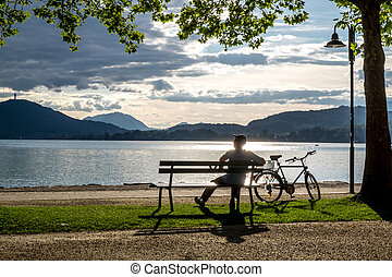 Man sitting on bench near lake and looks into the distance....