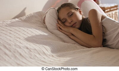 Funny little girl lying in bed smiling after sleeping,...