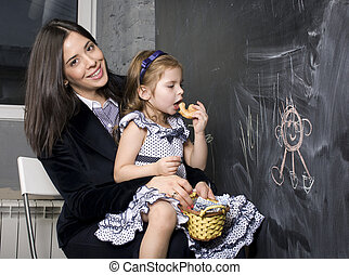 teacher with pupil in classroom at blackboard writting, mother and daughter first time to school