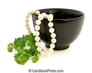 pearl and green leaves - white pearl in black bowl with...