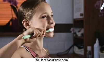 Child girl in pink pyjamas washing and brushing teeth in...