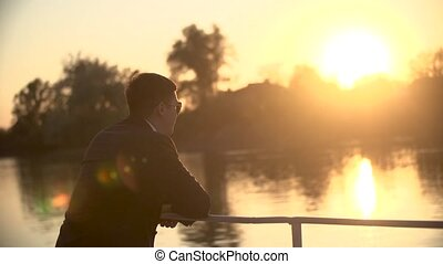 Business man standing on dock near lake or river
