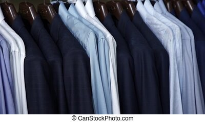 Row of men suit jackets and shirts on hangers shopping...