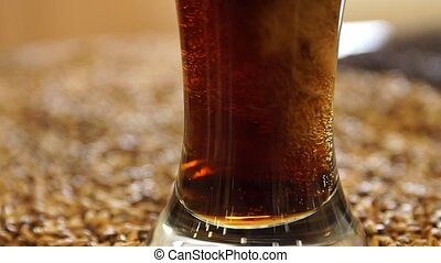 Dark lager beer pour into glass on a table with malt grain...