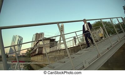 Businessman walking down the stairs to the river pier on the...