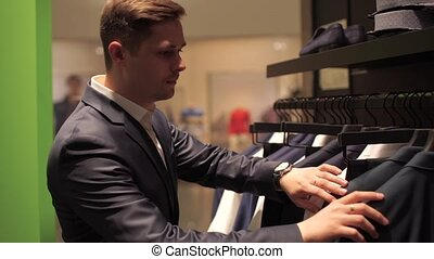 Man choosing business jacket from the raw in the shop. -...