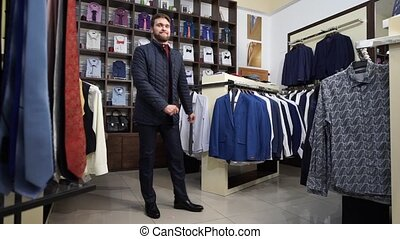 Young attractive man with a beard, dressed in a business suit, dancing in a men's clothing store.
