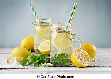 Lemonade with citrus in jars with handles closeup
