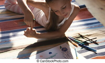 Pretty little girl drawing with color pencils on a floor in...