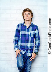 handsome boy - Portrait of a teenage boy standing by a white...