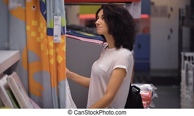 Pretty, young woman choosing curtains in shop