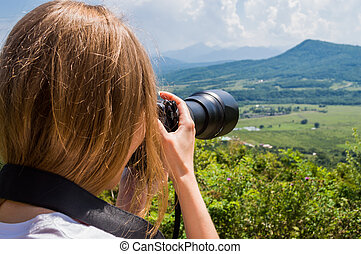 Woman taking picture with camera outdoor