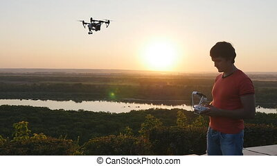 Man operating a drone with remote control. Dark silhouette...