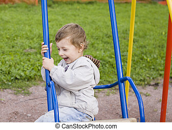 little cute boy playing on playground, hanging on gymnastic...