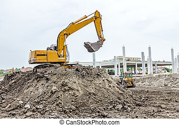 Excavator is preparing pile of ground for loading in truck...