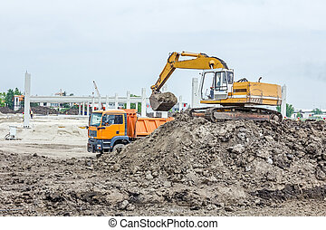 Excavator is loading a truck on building site - Yellow...