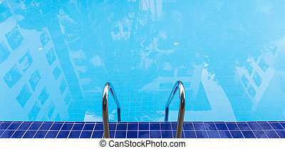 Blue swimming pool with shadow of building on water