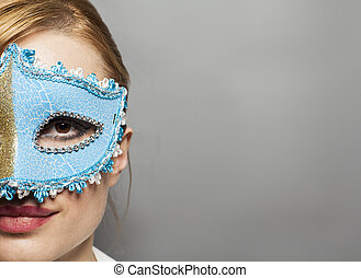 Beautiful young woman in mysterious venetian mask