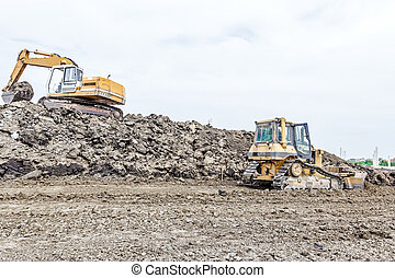 Heavy construction machinery is leveling building site -...