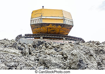 Back side of crawler excavator on pile of ground at building...