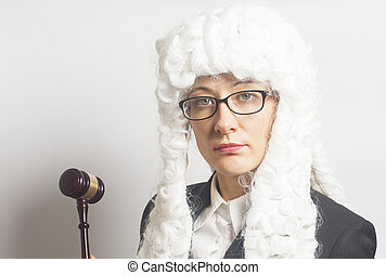 Female judge wearing wig and mantle with eyeglasses holding...