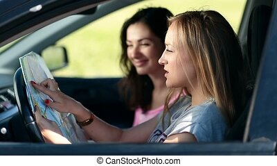Two pretty girls in car paving travel route on map - Side...