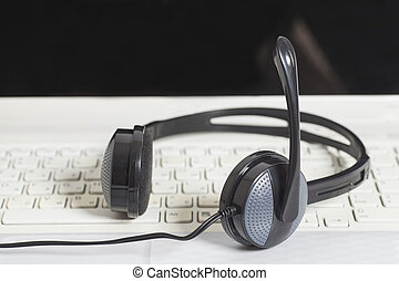 Headset with laptop computer keyboard.Communication concept