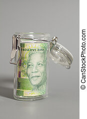 South African Rand in a glass jar on gray background