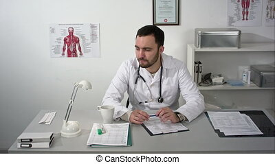 Thinking out loud. Thoughtful young bearded doctor in...