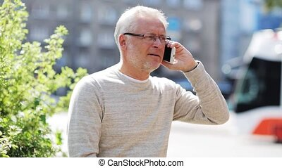 senior man calling on smartphone in city - technology,...
