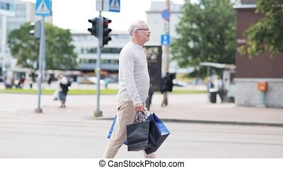 senior man with shopping bags walking in city - sale,...