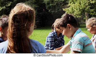 group of happy pre-teen playing outdoors - summer holidays,...