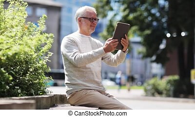 senior man having video call on tablet pc in city -...
