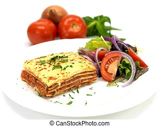 Lasagne plated up with a salad and isolated against a white...
