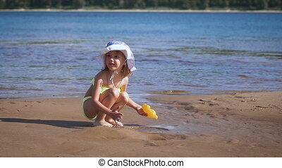 Cute little blonde girl playing with the sand at a lake -...