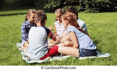 group of happy kids putting hands together - summer...