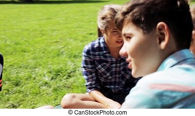 group of happy kids sitting on grass and talking - summer...