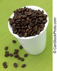 Coffee Beans - Coffee beans in a cup isolated against a...