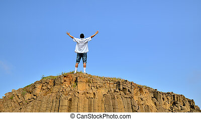 Man standing on cliff above blue sky - Man on top of...