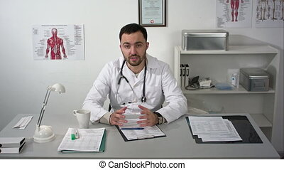 Bearded doctor quietly explaining to camera in medical...