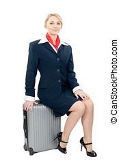 a stewardess - a pretty stewardess sitting on her suitcase...