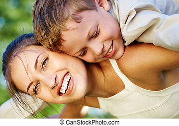 Excitement - Happy mother holding her cute son and laughing