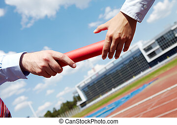 Passing turn - Photo of business people hands passing baton...