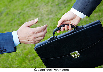 Career - Photo of human hands giving and taking a black...