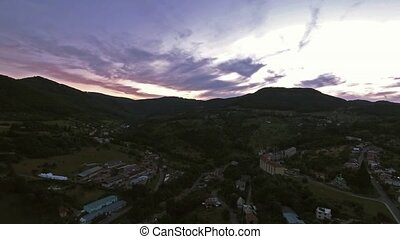 Aerial view of small town with hills at dusk.